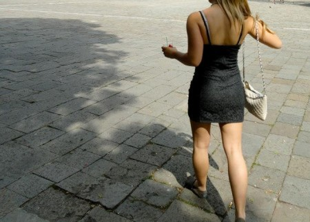 Woman-walking-brick-street-holding-drink