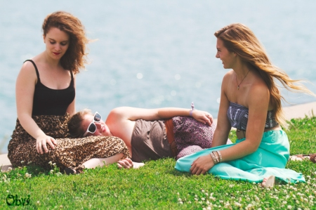 women lying in the grass near lake michigan in Chicago in the summertime