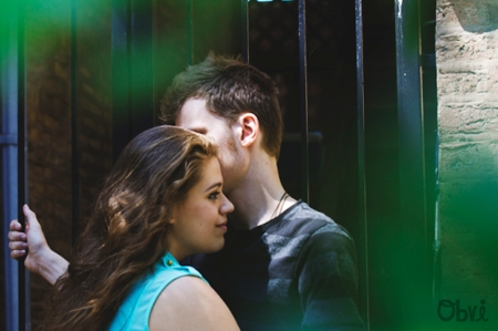 A man and a woman standing close to one another in a doorway