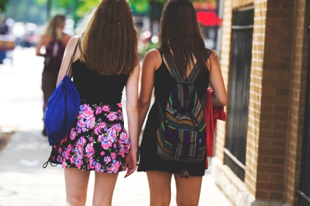 Two girls walking down the street in Chicago in the summer with backpacks