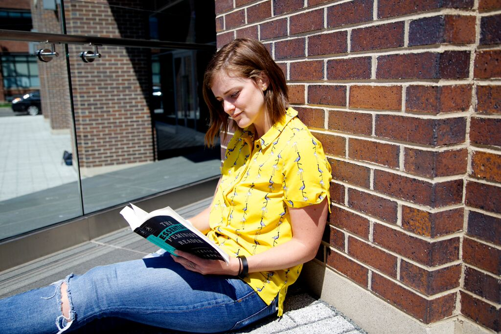 Yellow-shirt-book-reading-brick-wall