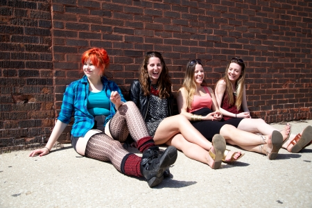 Women-sitting-brick-wall-laughing
