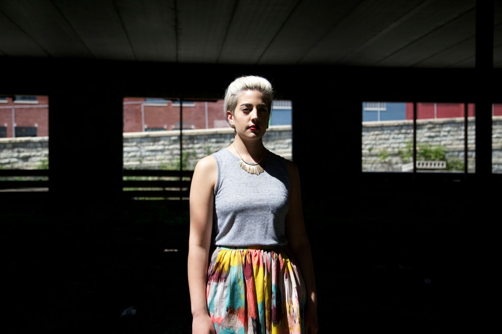 blonde woman in colorful skirt standing with light shining on her