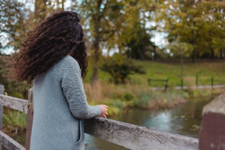 Woman with long dark, curly hair looking out at a river over a bridge